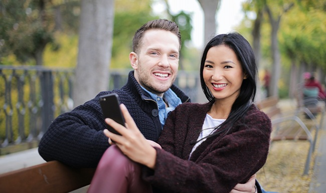 Couple siting on park bench