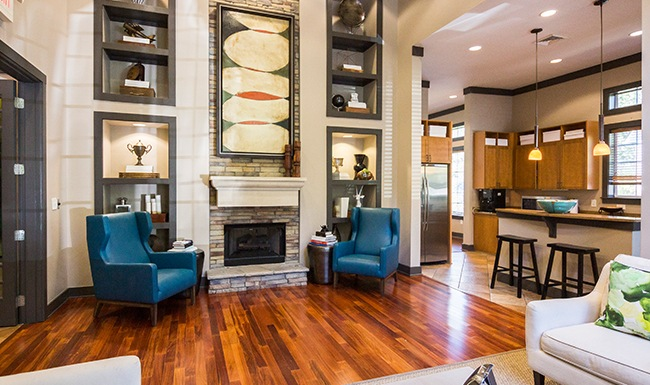 Well lit clubhouse with fireplace, large ceilings and plush seating